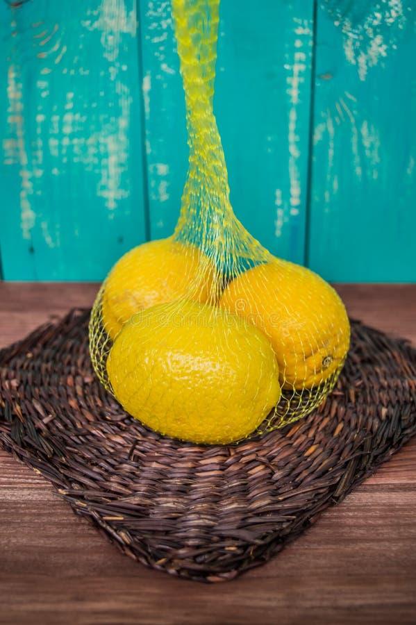 Limoni in una borsa della maglia fotografie stock