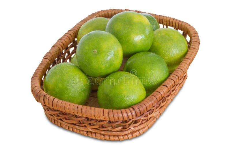 Limoni verdi in un canestro di vimini immagini stock