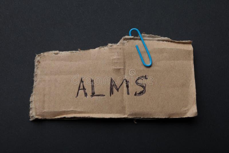 Limosnas de la palabra las 'en un pedazo de cartulina en un fondo negro imagen de archivo libre de regalías