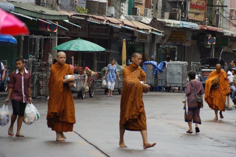 Limosnas de los monjes budistas en las calles del ` s de Bangkok fotos de archivo
