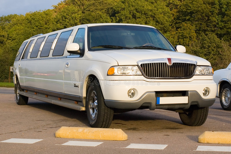 Limousine. White limousine parked in the street in warm setting sunlight royalty free stock photo