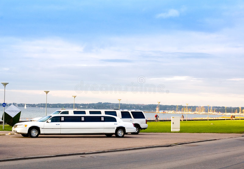Limousine. Two white limousine parked in the street near the sea in warm setting sunlight royalty free stock photography