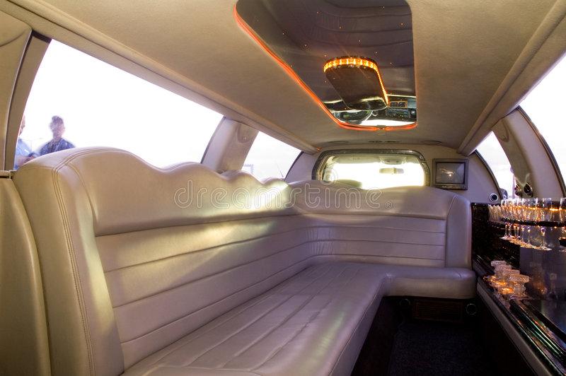 Limousine interior. View of a luxurious limousine interior with TV, mini bar and leather seats stock photo