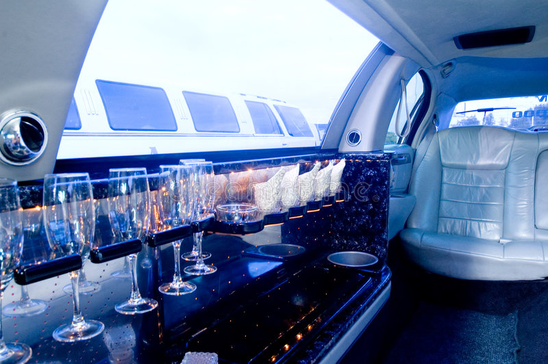 Limousine interior. View of a luxurious limousine interior with a mini bar and leather seats. Slight blue cast for business-like looks stock photography