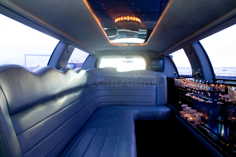 Limousine interior. View of a luxurious limousine interior with a TV-set, mini-bar and leather seats royalty free stock photo