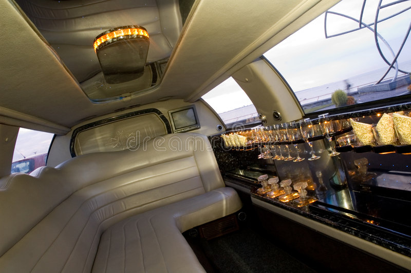 Limousine interior. View of a luxurious limousine interior with a TV-set, mini-bar and leather seats stock image