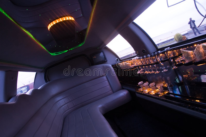 Limousine interior. View of a luxurious limousine interior with a TV-set, mini-bar and leather seats. Low key, outside light only stock images