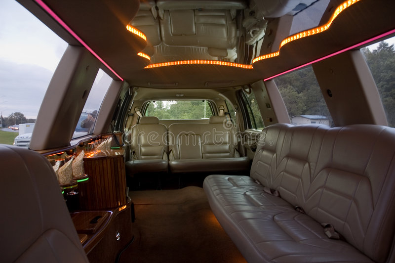Limousine interior. View of a luxurious jeep-limousine interior with a TV-set, mini-bar and leather seats. Low key, outside light only stock image