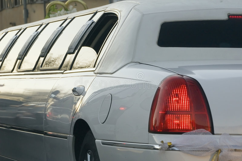 Limousine for wedding. Wedding limousing moving on city streets at evening time royalty free stock photo