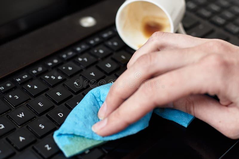 Limpa a mão café derramado no teclado do laptop com um pano fotos de stock