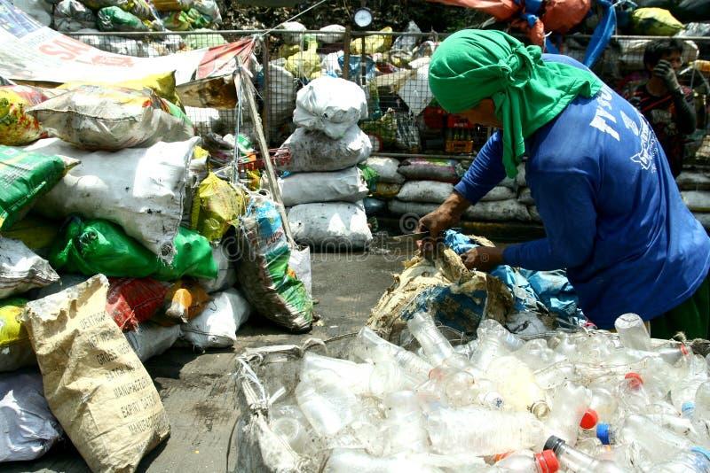 Limpador que classifica através do lixo em um local da descarga em Manila, Filipinas para procurar coisas recicláveis foto de stock