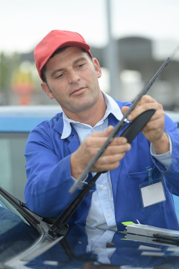 Limpadores de pára-brisas em mudança do homem no carro foto de stock royalty free