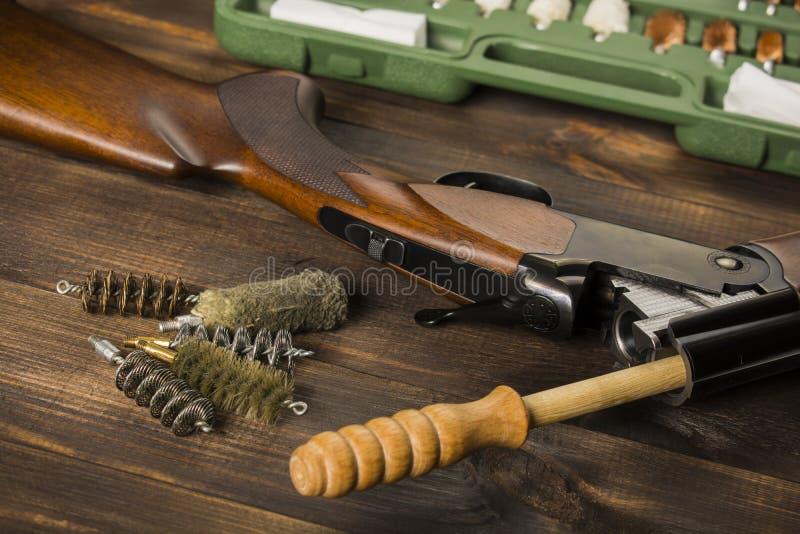 Limpando a arma em uma tabela de madeira imagens de stock royalty free