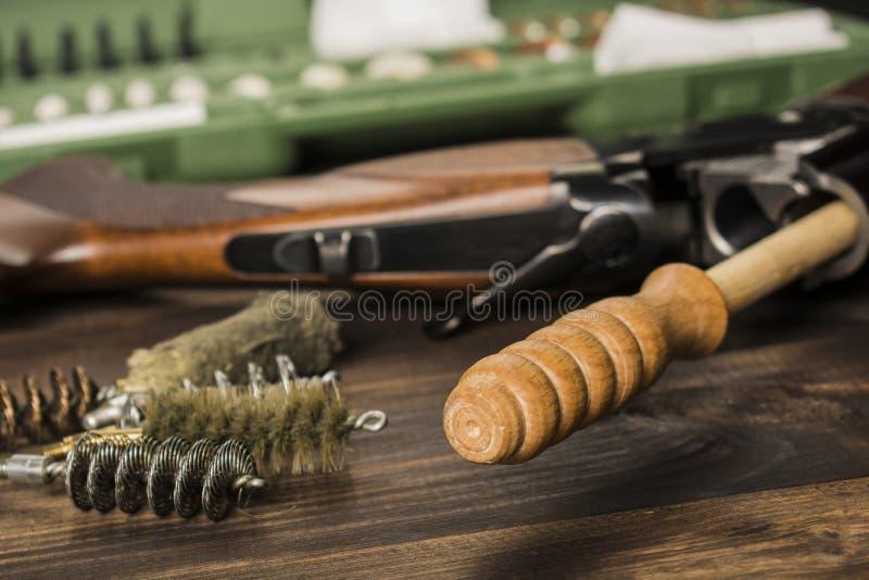 Limpando a arma em uma tabela de madeira fotografia de stock royalty free