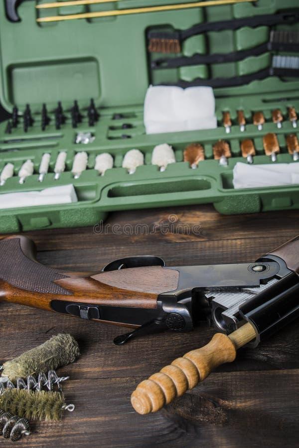 Limpando a arma em uma tabela de madeira foto de stock royalty free