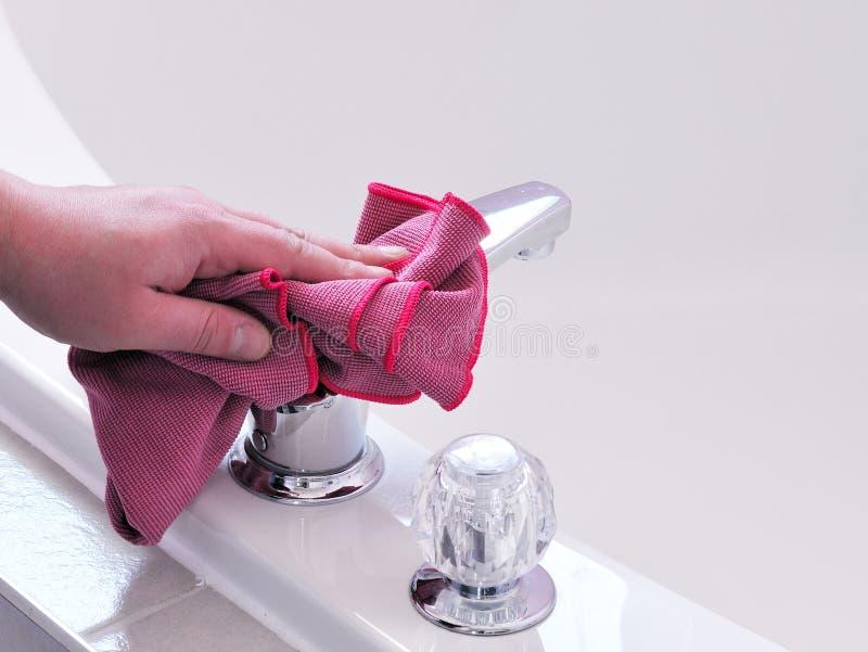Limpando a cuba e a torneira de banho imagens de stock royalty free