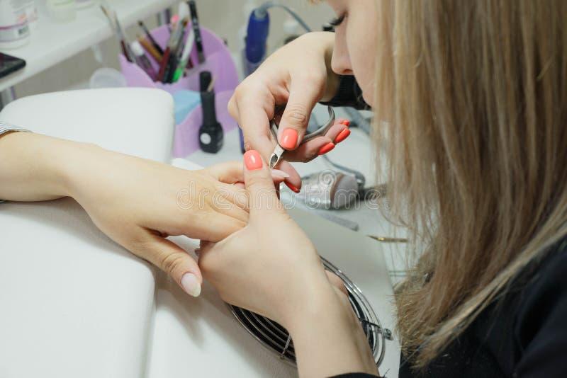 Limpando e nivelando a cutícula com as pinças na raiz das unhas imagem de stock