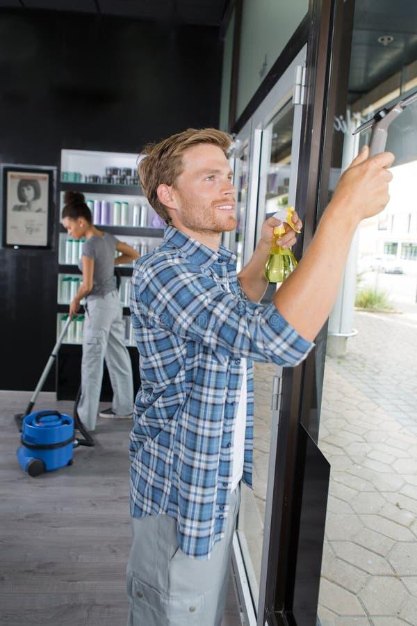 Limpando a janela de vidro foto de stock