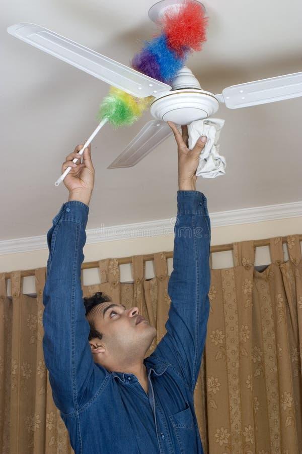 Limpando o ventilador de teto fotografia de stock