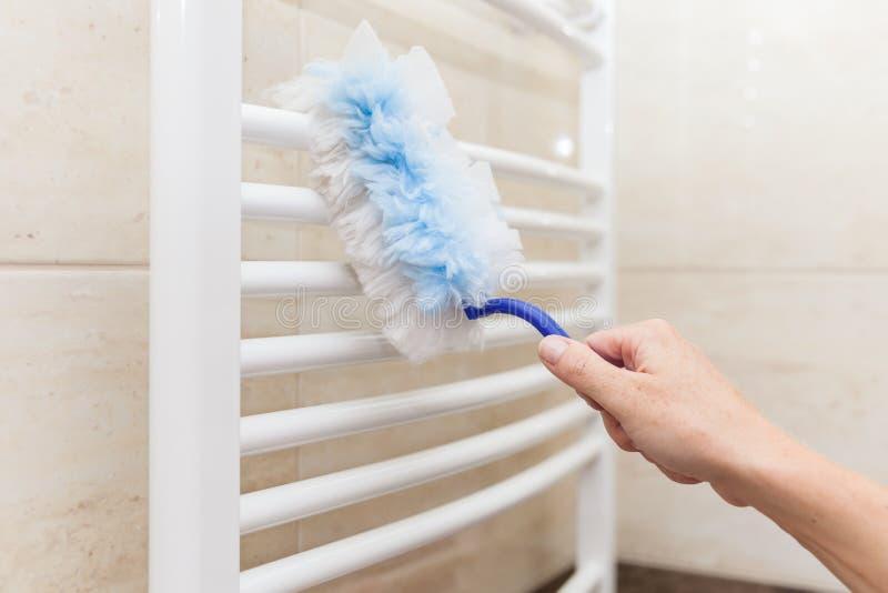 Limpando a poeira na casa com um pano fotografia de stock royalty free