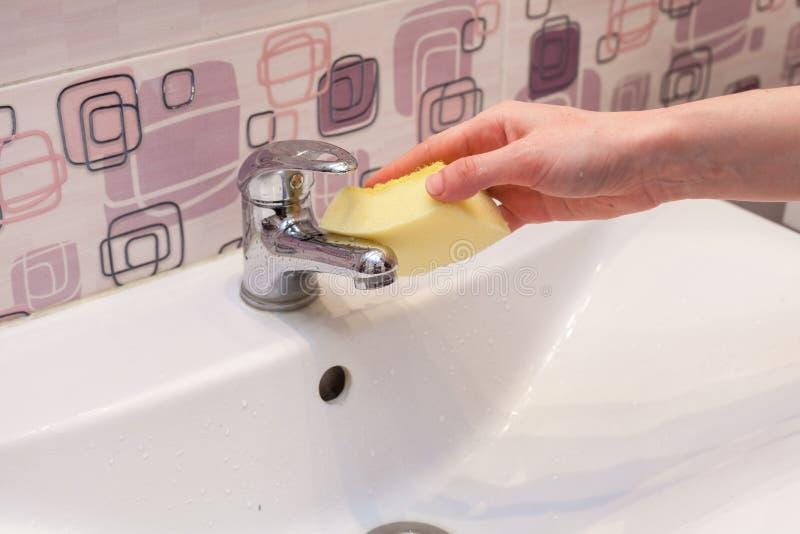 Limpando um banheiro novo do metal bata com esponja amarela imagem de stock
