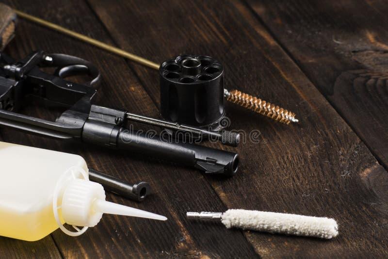 Limpando um revólver antigo em uma tabela imagem de stock