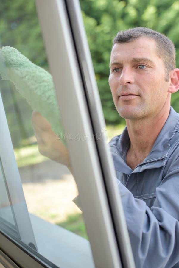 Limpando uma janela de vidro fotos de stock royalty free
