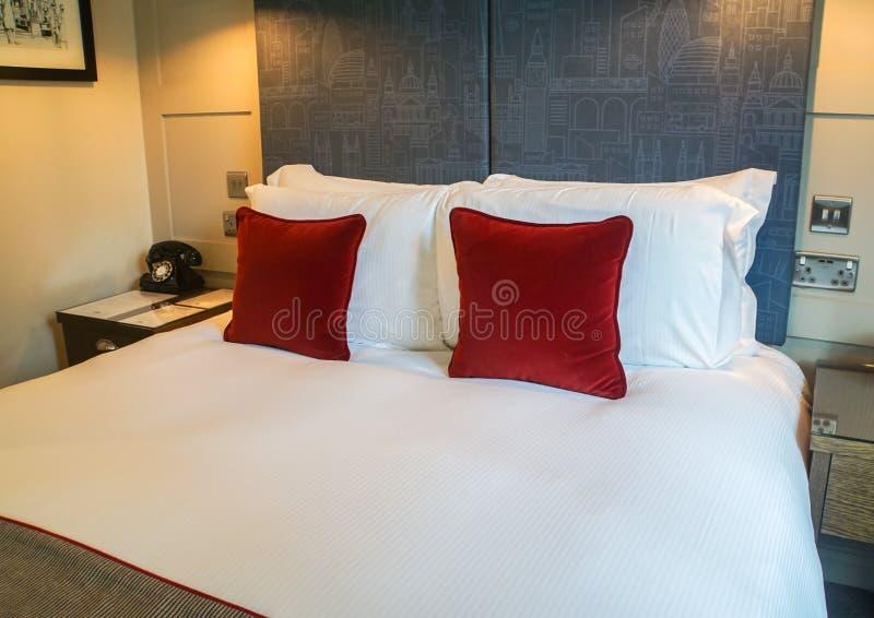 Limpe a cama enorme luxuosa com muitos descansos na sala de hotel mestra imagens de stock