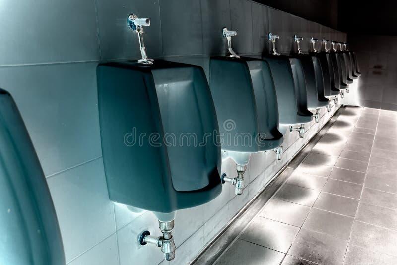 Limpe homens dos mictórios no toalete do posto de gasolina fotografia de stock