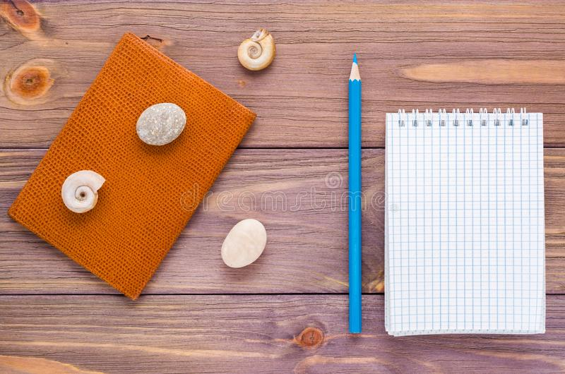 Limpe o bloco de notas aberto para a escrita, o lápis, o passaporte e a concha do mar imagem de stock royalty free