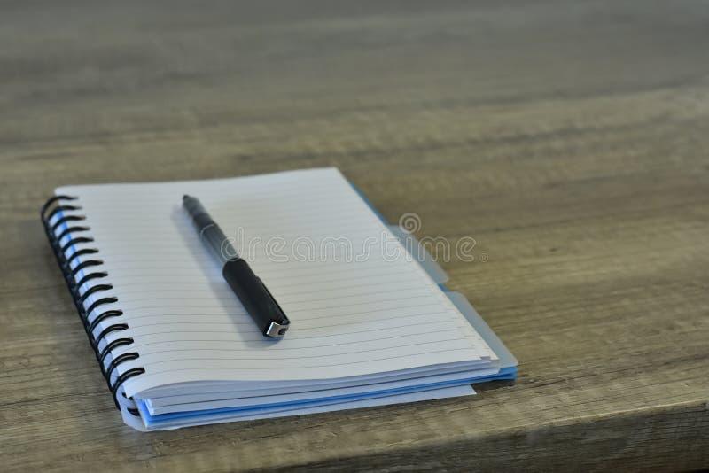Limpe o bloco de notas com uma pena em uma mesa de madeira imagens de stock