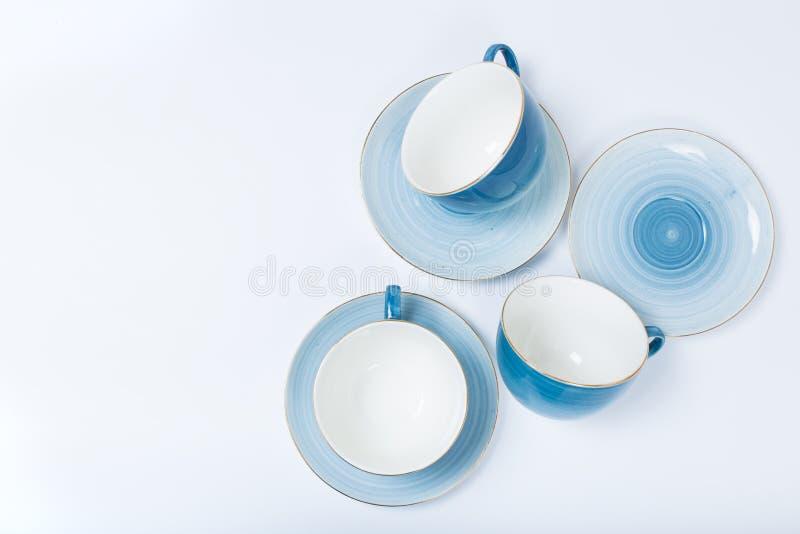 Limpe o grupo dos pratos, do café ou de chá Abundância de copos e de pires elegantes da porcelana no fundo branco imagens de stock royalty free