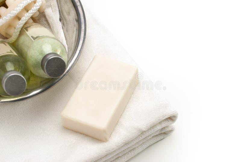 Limpe a toalha branca com as loções do banheiro e a bacia do banho fotografia de stock