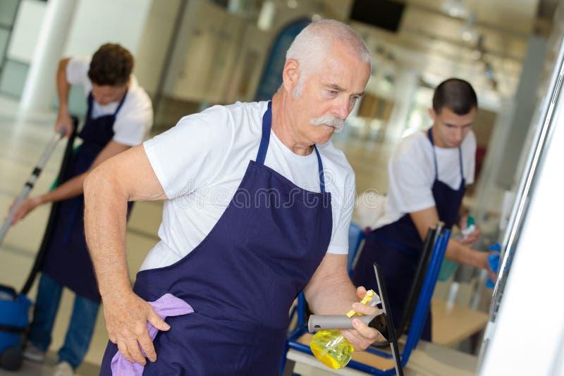 A limpeza bem sucedida dos trabalhos de equipa presta serviços de manutenção a trabalhadores imagem de stock royalty free