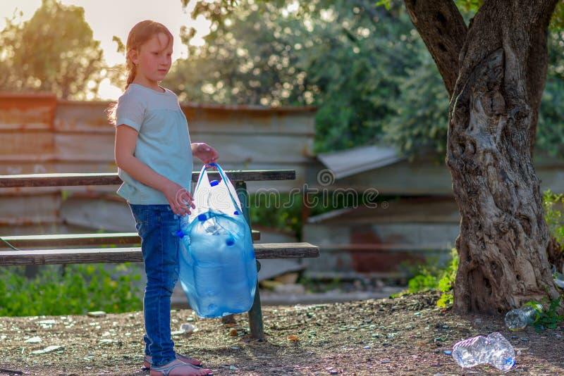 Limpeza da crian?a no parque Crian?a volunt?ria com um saco de lixo que limpa a maca, pondo a garrafa pl?stica em reciclar o saco imagens de stock