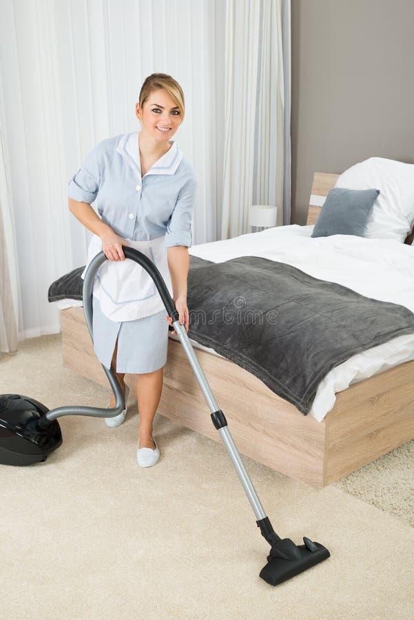 Limpeza da empregada com aspirador de p30 fotografia de stock royalty free