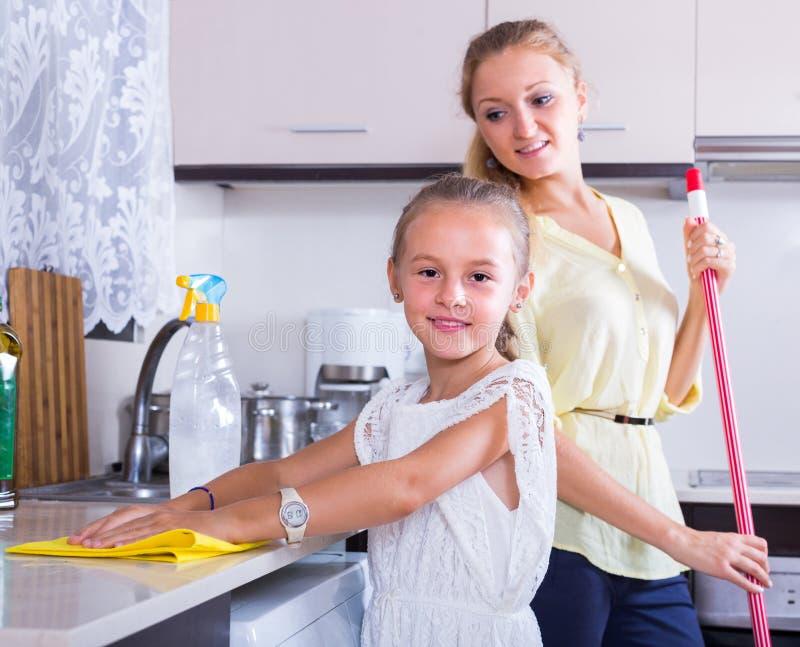 Limpeza da menina e da mulher na cozinha foto de stock