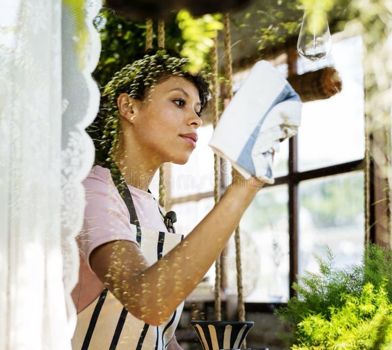 Limpeza da mulher da ascendência africana que limpa o vidro da loja foto de stock royalty free