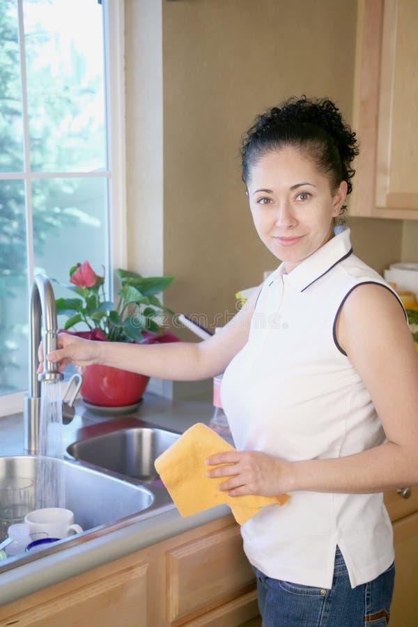 Limpeza da mulher na cozinha imagem de stock