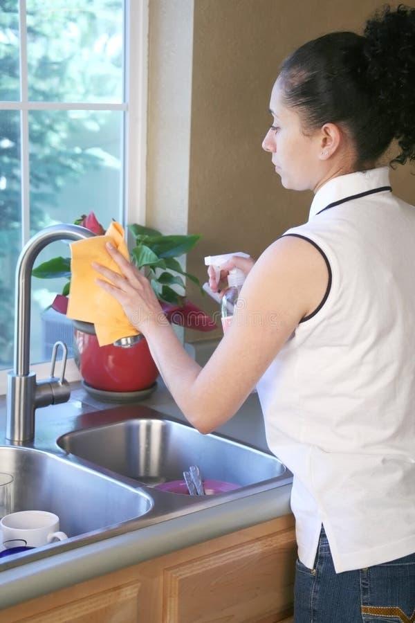 Limpeza da mulher na cozinha fotos de stock