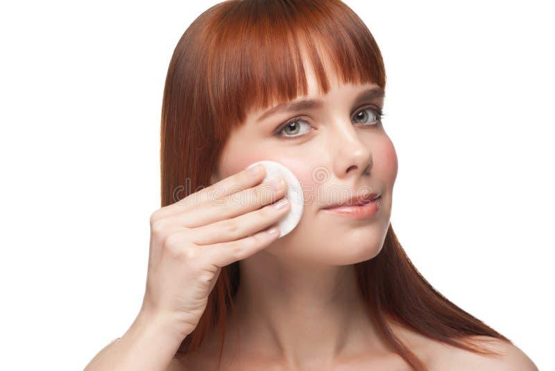 Limpeza da mulher nova sua face fotografia de stock