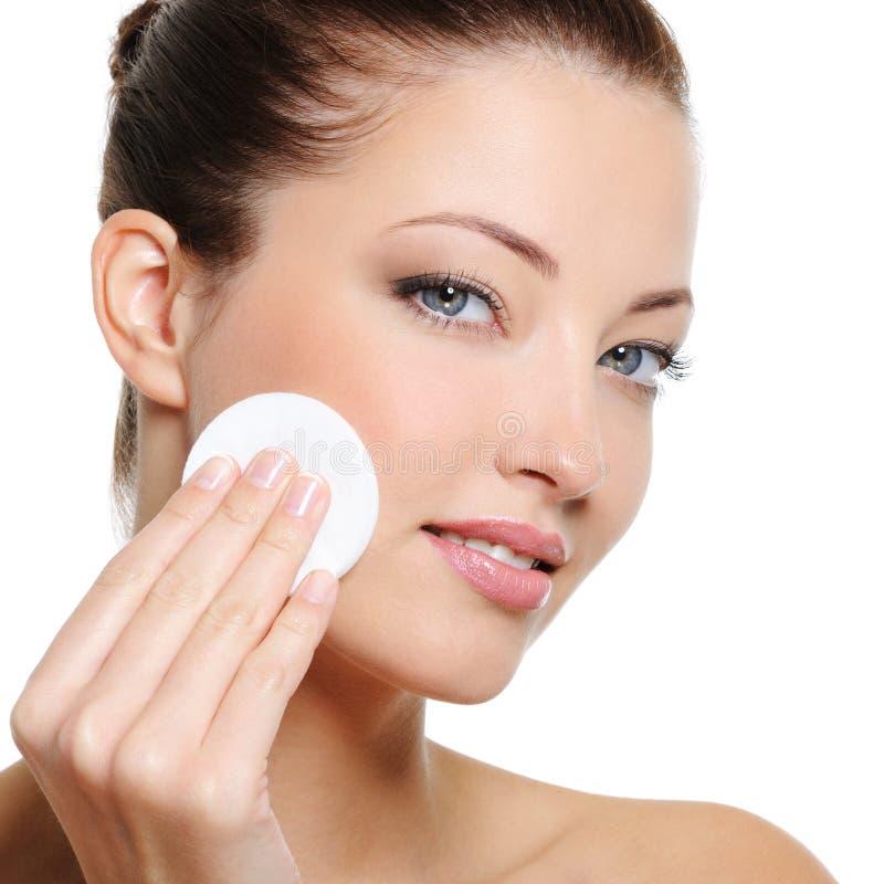 Limpeza da mulher sua face com cotonete de algodão fotografia de stock