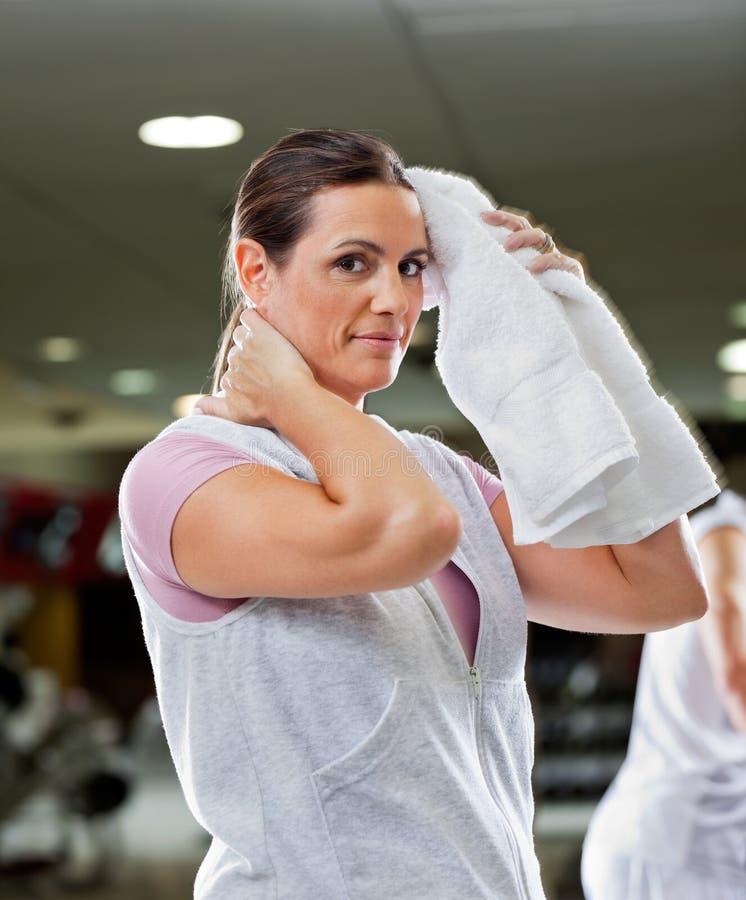 Limpeza da mulher suada com a toalha no health club imagem de stock