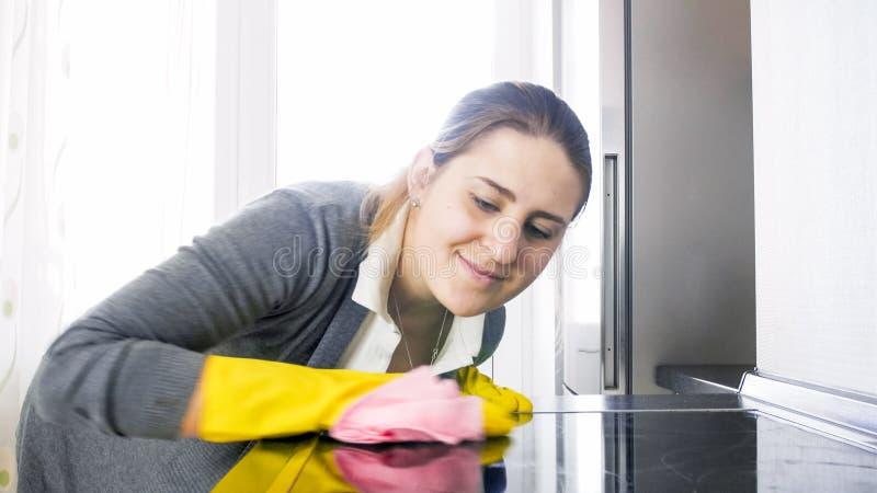 A limpeza de sorriso bonita da dona de casa manchou a superfície dos glas do hob bonde fotos de stock royalty free