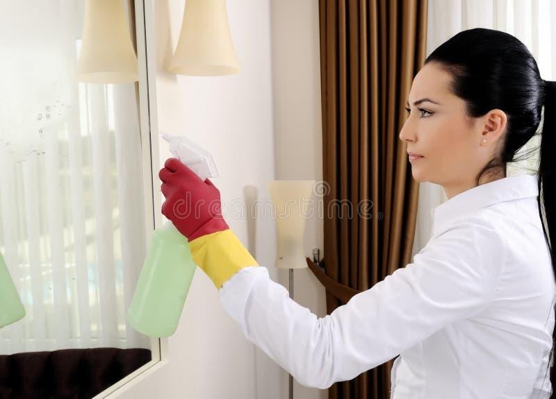 Limpeza do espelho das mulheres novas fotografia de stock