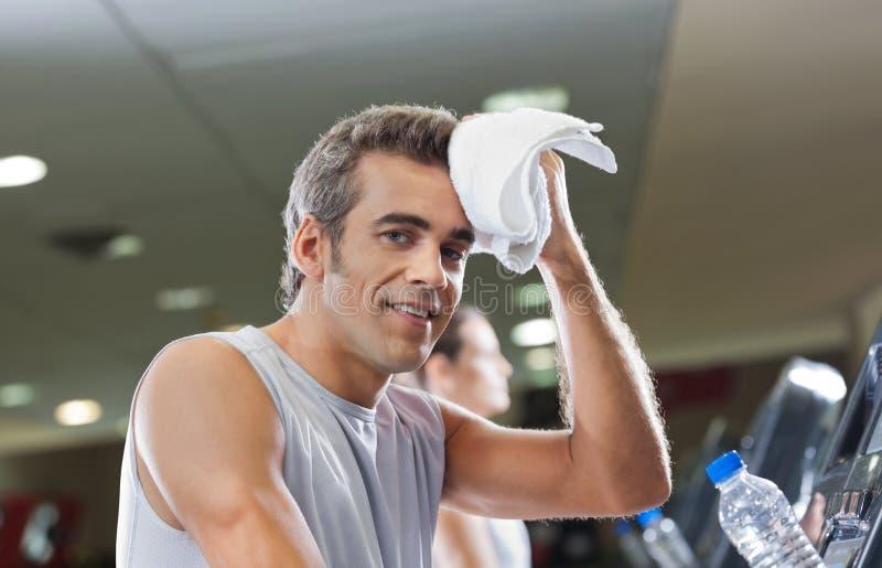 Limpeza do homem suada com a toalha no health club fotografia de stock
