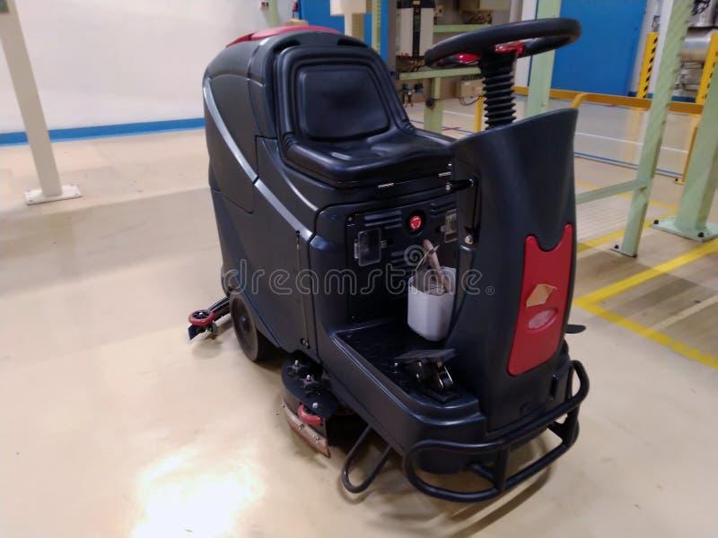 Limpeza profissional do assoalho, máquina que limpa, manutenção do assoalho da fábrica foto de stock