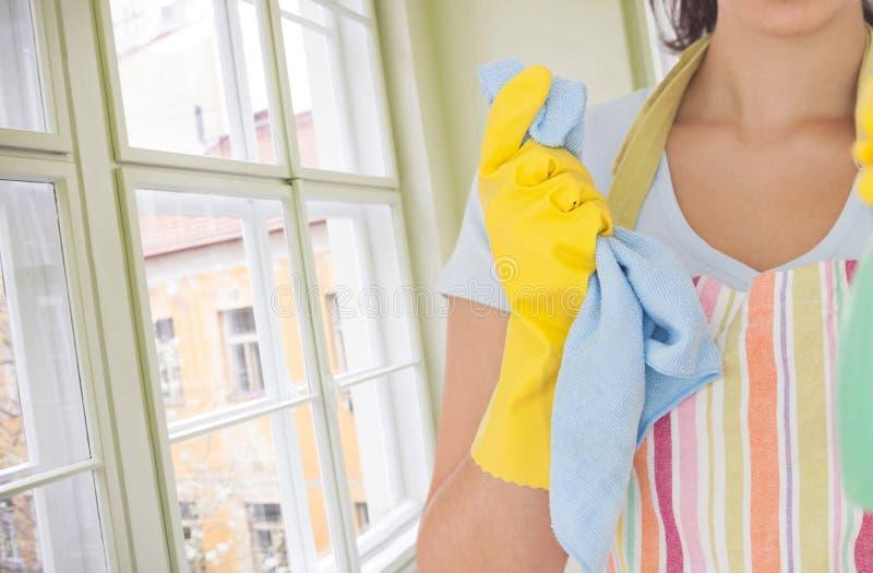 Limpiador de la mujer contra una ventana en el cuarto fotos de archivo