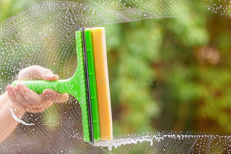 Limpiador de ventana que usa un enjugador para lavar una ventana Barra horizontal limpia fotografía de archivo libre de regalías
