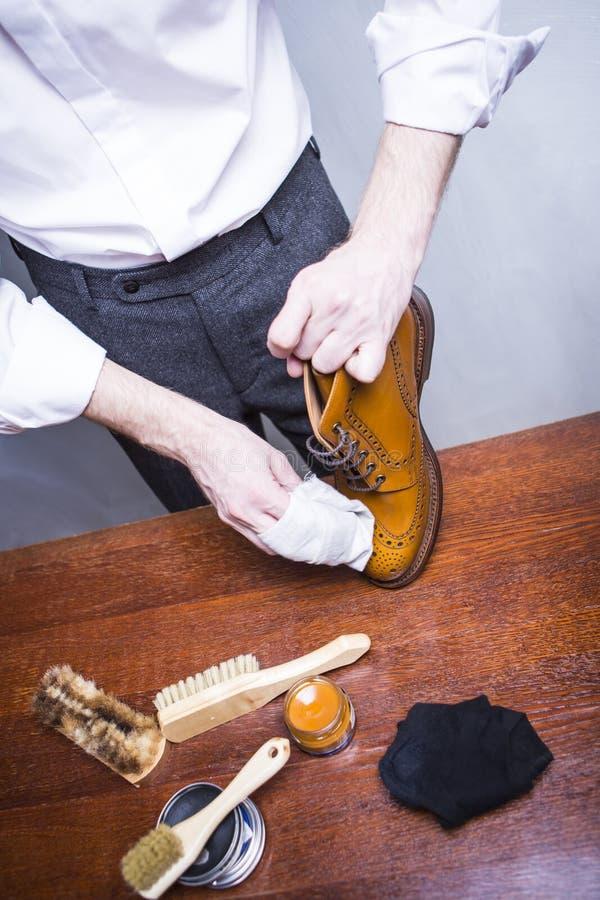 Limpiador de zapatos masculino que usa el cepillo para Tan Brogue Derby Boots masculina de pulido foto de archivo libre de regalías